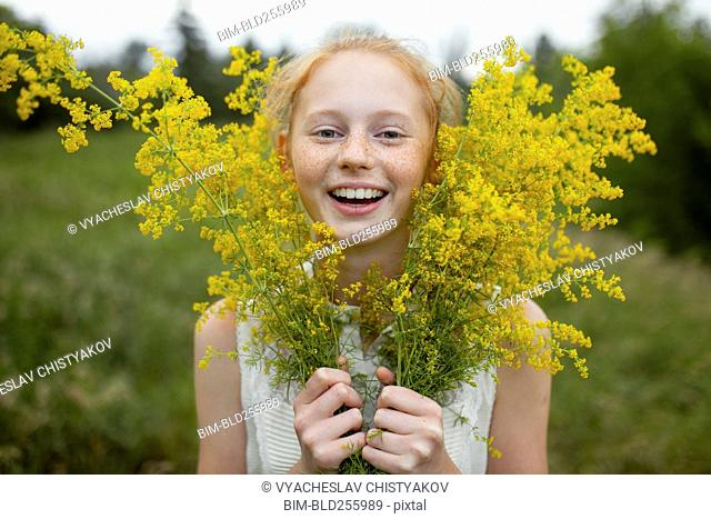 Portrait of smiling Caucasian girl with freckles holding wildflowers