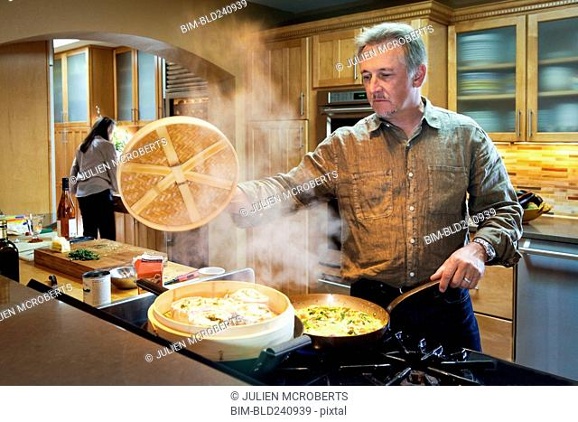 Caucasian man steaming food on stove