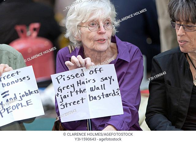 A woman holds a protest sign in Zuccotti Park reading 'Pissed off grey hairs say, jail the Wall Street bastards' during the Occupy Wall Street demonstration in...