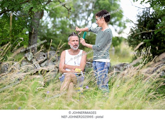 Woman cutting man hair in garden