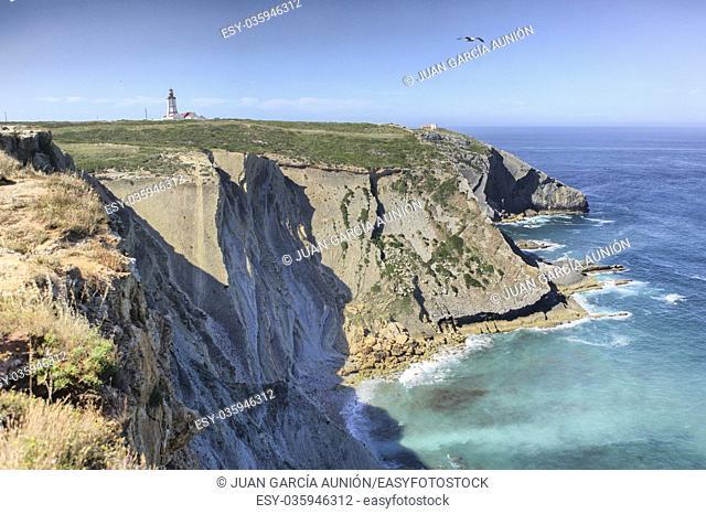 Espichel Cape lighthouse building over rocky cliffs, Sesimbra, Portugal