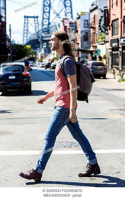 USA, New York City, man crossing the street in Williamsburg, Brooklyn
