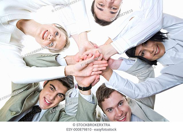 Below shot of smiling co-workers making pile of hands and looking at camera