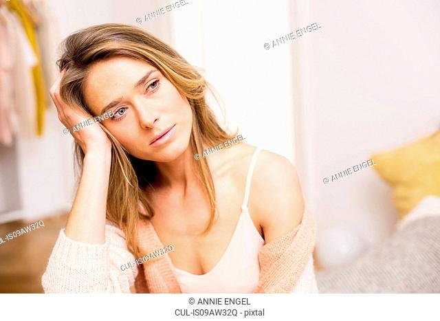 Mid adult woman sitting on bed with hand on head