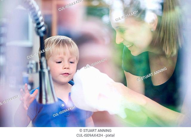 Mother and son doing washing up together, playing with bubbles