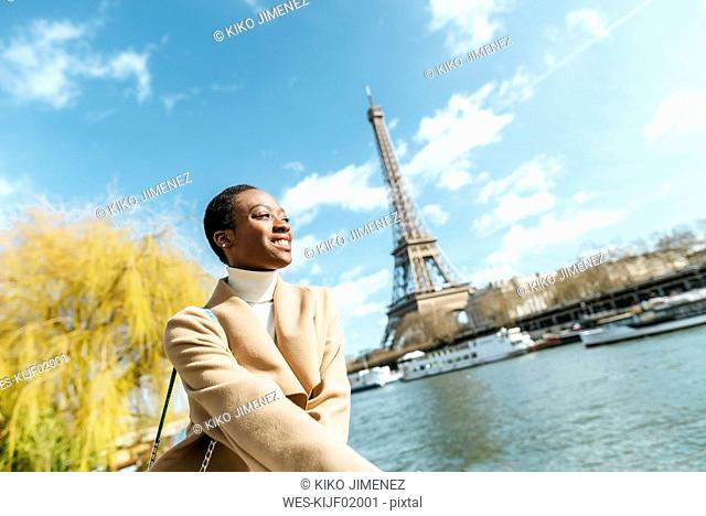 France, Paris, Smiling woman at river Seine with the Eiffel Tower in the background