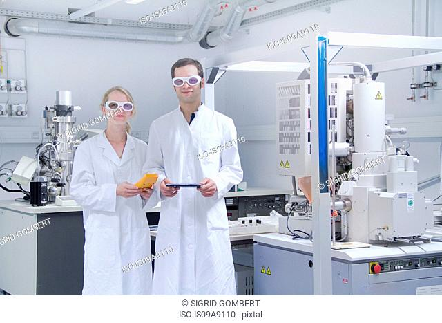 Two scientists wearing lab coats standing in laboratory