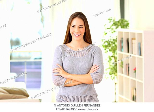 Portrait of a proud homeowner posing looking at you standing in the living room at home