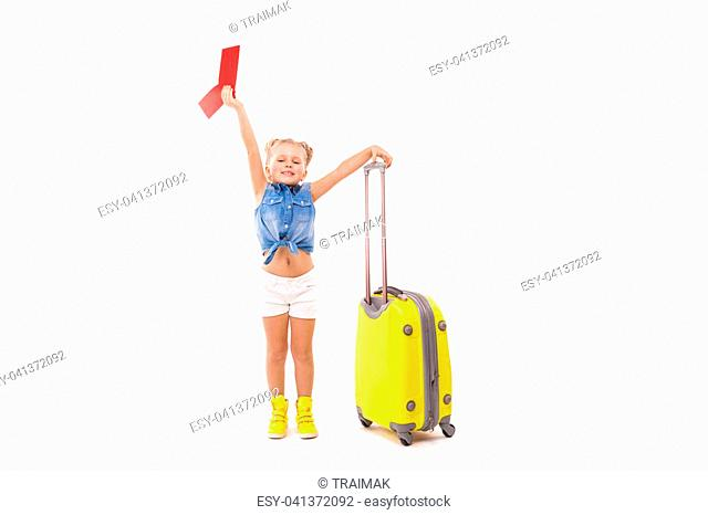 Isolated on white, beauty caucasian blonde girl in blue shirt, white shorts, sunglasses and yellow boots hold yellow suitcase by the handle, look at camera