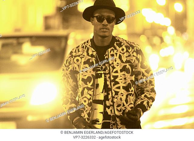 fancy blogger man at city street at night, wearing stylish outfit, car lights, traffic, cool attitude, in Munich, Germany