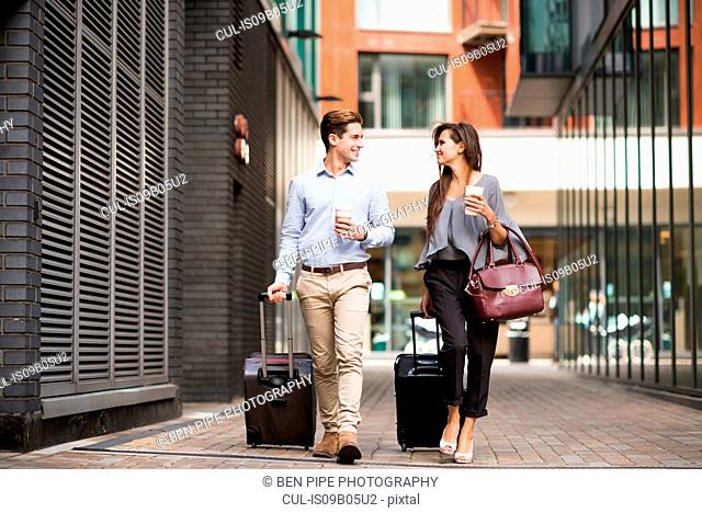 Young businessman and woman with wheeled suitcases walking and talking, London, UK