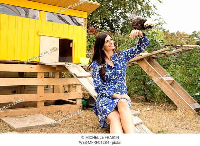 Smiling woman with Polish chicken at chickenhouse in garden