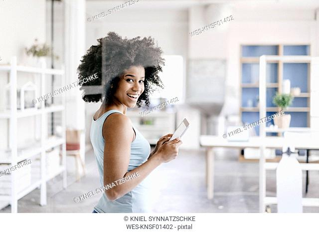 Young woman using digital tablet in her new office