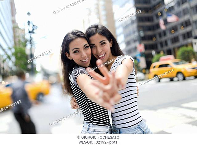 USA, New York City, portrait of two beautiful twin sisters in Manhattan having fun