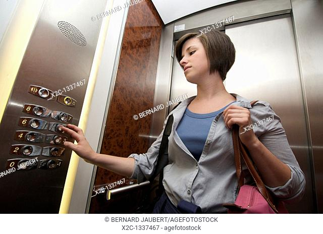 Young woman pressing on a button in an elevator