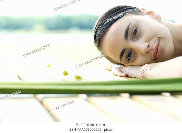 Woman lying on deck, surrounded by flowers and foliage