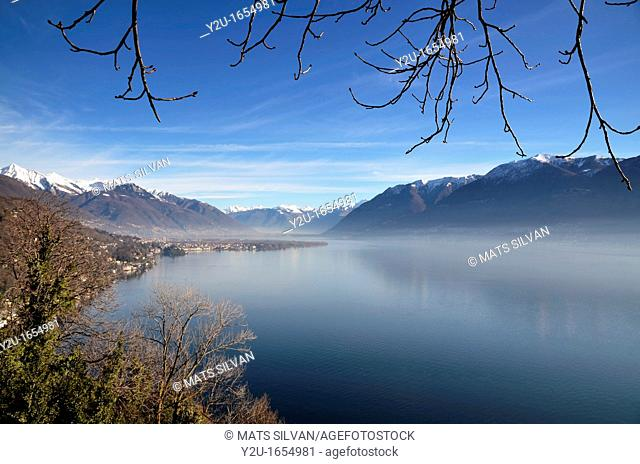Foggy lake in the alps with snow on tops of the mountains and a misty sunny day