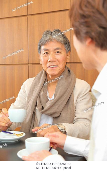 Fashionable Japanese senior couple enjoying a cup of coffee