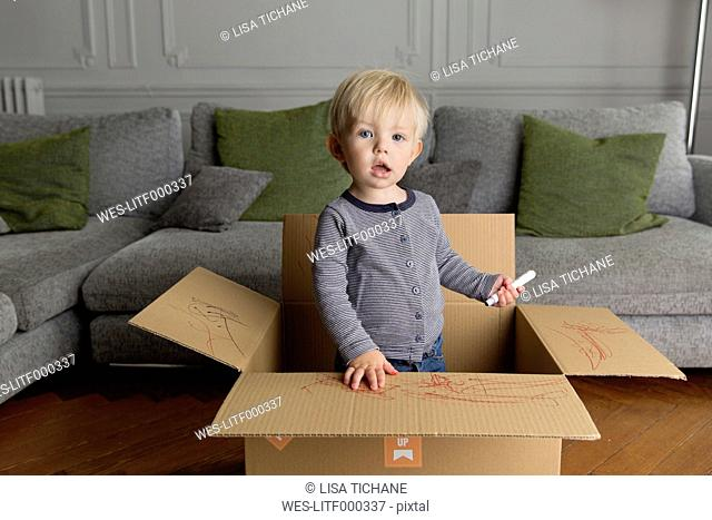 Portrait of toddler with marker standing in a cardboard box