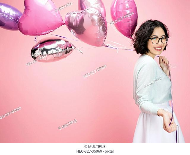 Portrait smiling young brunette woman carrying heart-shape bunch balloons against pink background