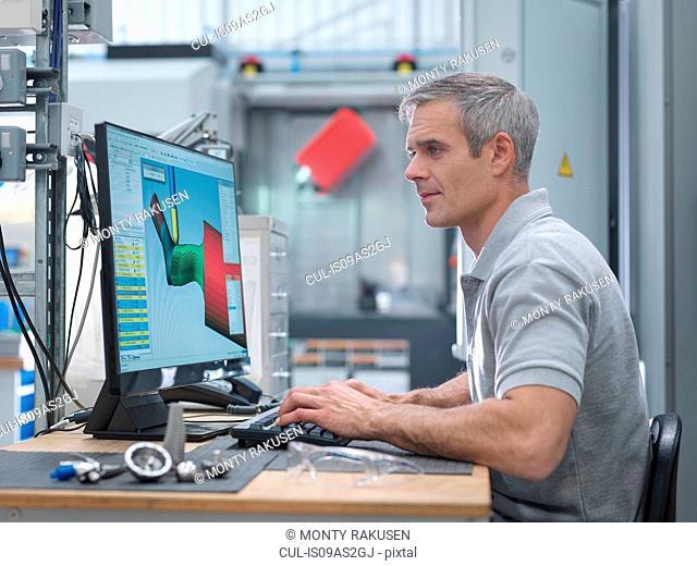 Engineer watching CNC lathe progress on screen in orthopaedic factory