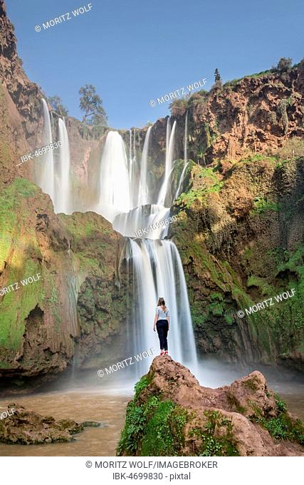 Young woman standing on a stone in front of Ouzoud waterfalls and cascades, Cascades d'Ouzoud, River Oued Tissakht, Middle Atlas, Azilal Province, Morocco