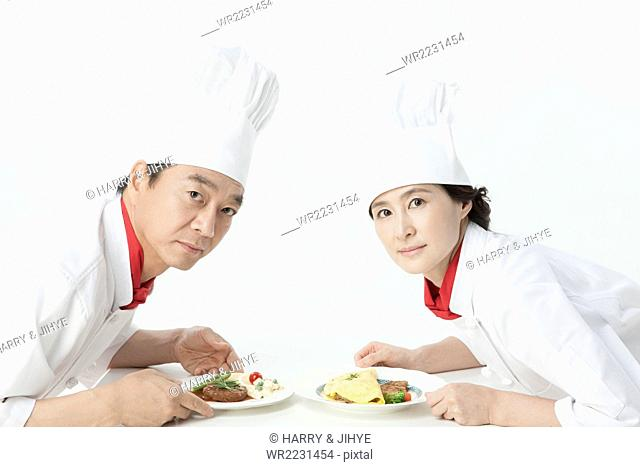 Middle aged male and female cooks facing each other and holding a dish each in rival