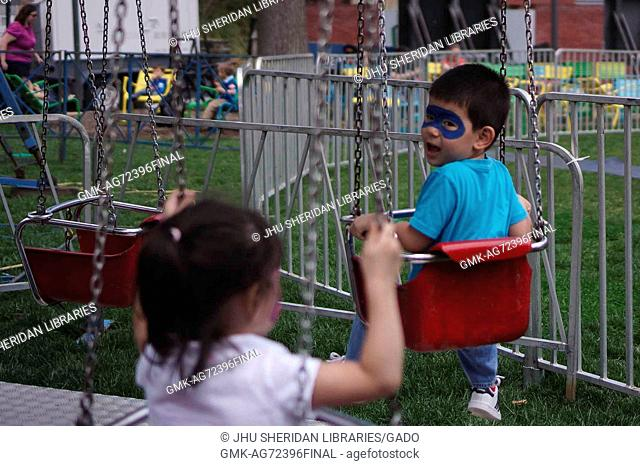 A toddler with face-paint on a small swing ride glances back at his sister in a swing behind him at Spring Fair, a student-run Spring carnival