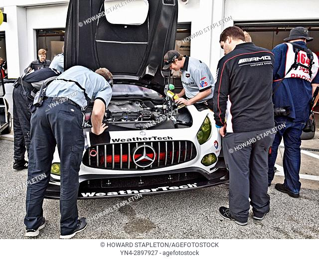 Mechanics work on a Mercedes AMG GT3 entered by Riley Motorsports prior to the start of the 24-hour Rolex endurance race at Daytona Beach, Florida in 2017