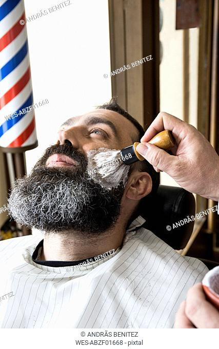 Barber putting shaving foam in man's beard
