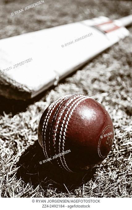 Tone vintage still-life photo of a worn red cricket ball and wood bat. Historical sports