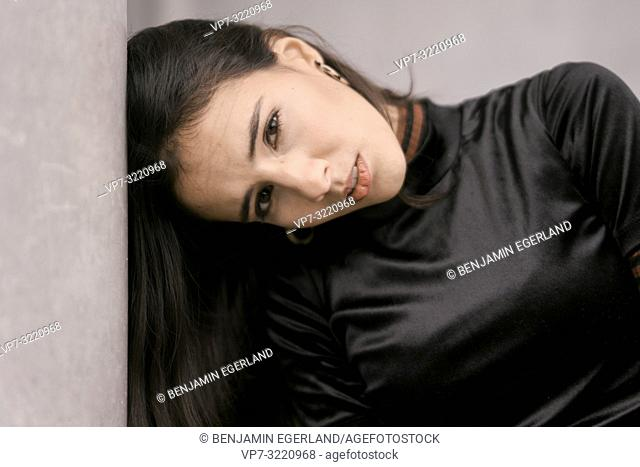 portrait of emotional woman leaning head against wall, in Munich, Germany