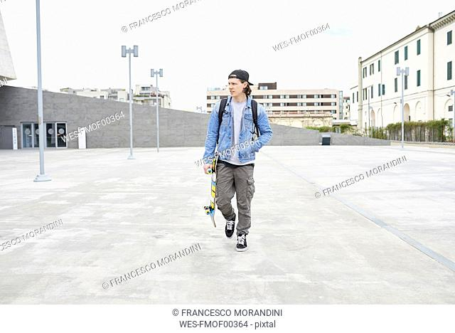 Young man walking in the city, carrying skateboard