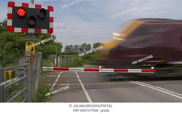 Train passing an automatic level crossing at speed then the barriers open 4:2:2