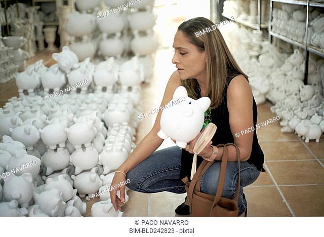 Hispanic woman crouching in store holding piggybank