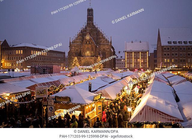 Visitors walk in between the stands of the Christkindlesmarkt during snowfall in Nuremberg, Germany, 03 December 2017. Photo: Daniel Karmann/dpa