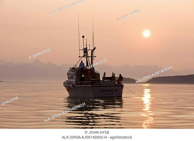 A commercial Gill net vessel makes its last set for the day in the waters of Lynn Canal with Chilkat Mountains in the background, Inside Passage, Southeast