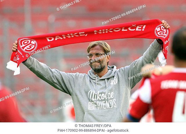 "dpatop - Liverpool coach Juergen Klopp holds a football scarf that reads """"Dank, Nikolce"""" (lit. thanks, Nikolce) at the FSV Mainz 05 vs """"Nikolce and friends""""..."