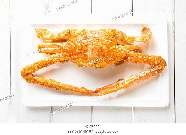 Close up top view cooked delicious hot and spicy sauce blue crab on white plate. Fresh cook with hot smoke steams
