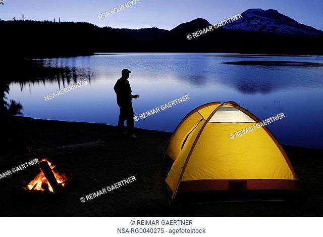 Camper with mug on Sparks Lake shore