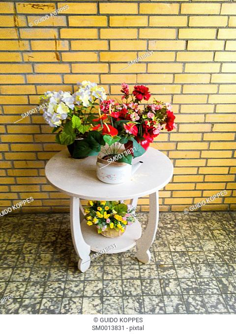 Zwijndrecht, Netherlands. Sidetable with pots of flowers inside a multi floor apartment building, decorating stairs and entrance to apartments