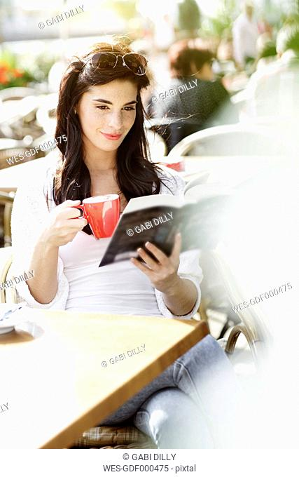 Smiling young woman reading a book at a pavement cafe