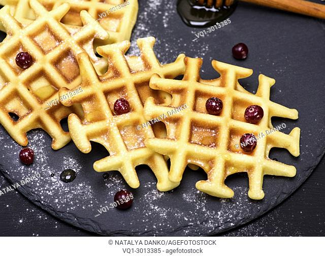 baked waffles on a black background, top view