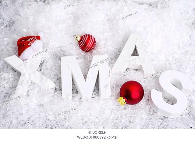Red Christmas baubles and white letters building the word 'XMAS' lying in artificial snow