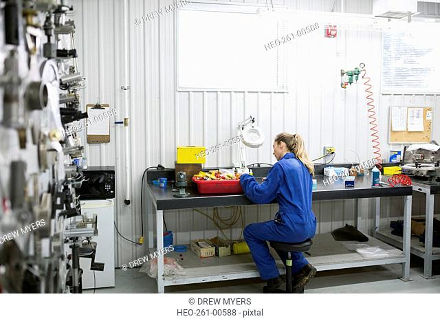 Female helicopter mechanic at workbench