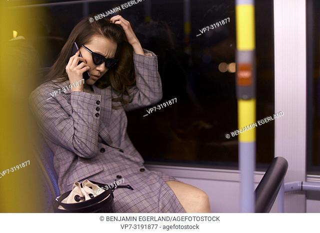 Woman in tram by night, talking by phone. Munich, Germany