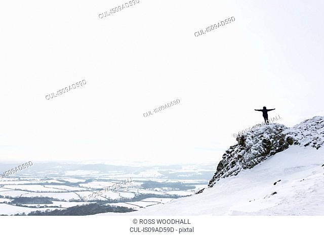 Woman standing on The Wrekin in winter, Shropshire, England, UK