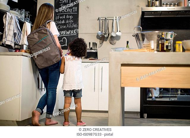 Sisters looking up at blackboard in kitchen