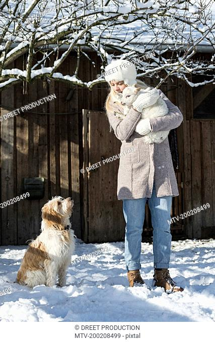 Teenage girl standing in front of barn with lamb and dog during winter, Bavaria, Germany