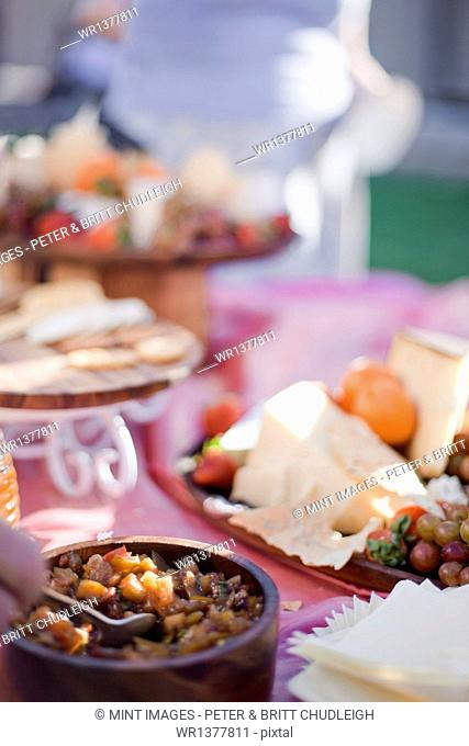 A table laid with a buffet selection of food dishes. Desserts and cheese board